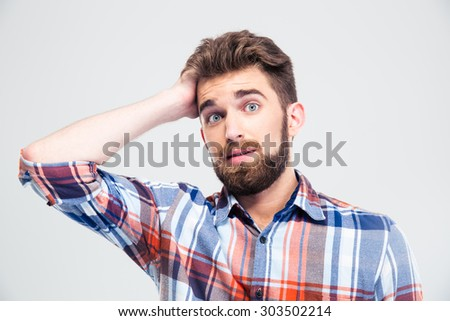 Portrait of amazed young man looking at camera isolated on a white background - stock photo