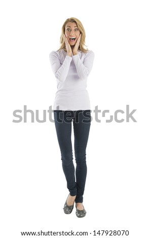 Portrait of amazed young woman screaming while standing against white background - stock photo