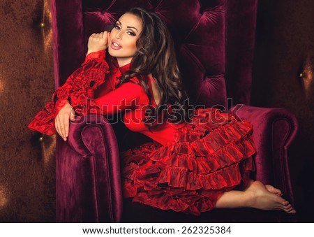 Portrait of amazing beautiful sexy brunette woman with lovely plump lips in red tango dress posing sitting in a velvety armchair dreaming, smiling and looking at camera. Dark brown luxury background