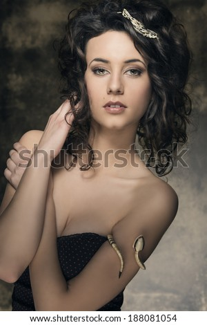 portrait of amazing brunette woman with sexy low-necked dress, creative jewels and cute curly hair-style. Fashion elegant portrait
