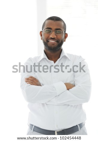 Portrait of American African business man smiling with arms crossed over white background - stock photo