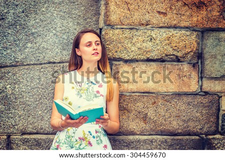 Portrait of American college student. A pretty girl wearing flower patterned, sleeveless, white dress, holding green book, standing by rocky wall, narrowing eyes, reading, thinking. Instagram effect. - stock photo
