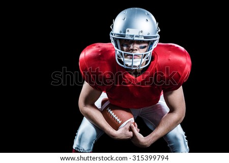 Portrait of American football player bending while holding ball against black background - stock photo
