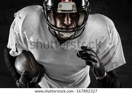 Portrait of american football player holding a ball and running