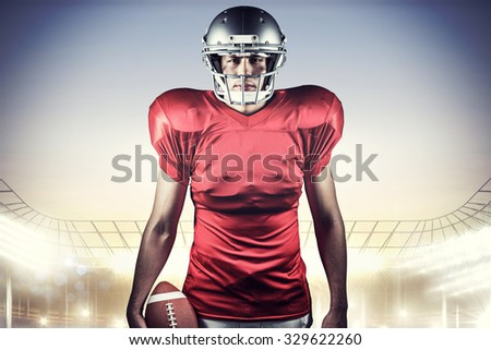 Portrait of American football player holding ball against rugby stadium