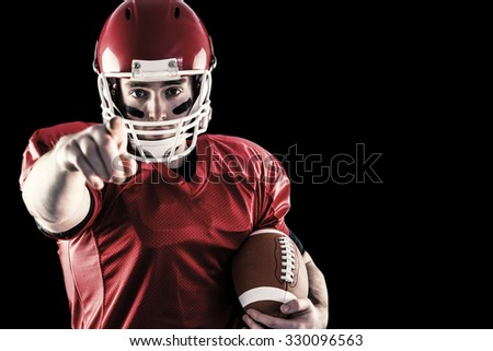 Portrait of american football player holding football and pointing to camera against black