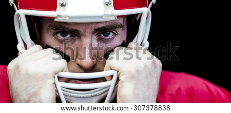 Portrait of american football player holding onto his helmet against black background - stock photo