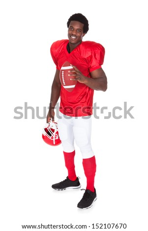 Portrait Of American Football Player Holding Rugby Ball Over White Background