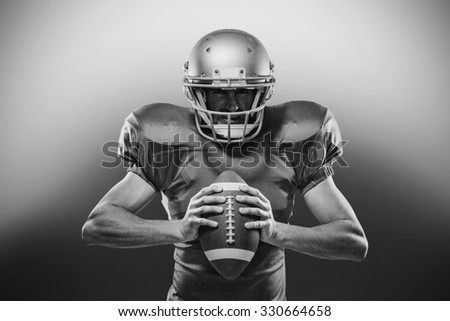 Portrait of American football player in red jersey and helmet holding ball on white background - stock photo