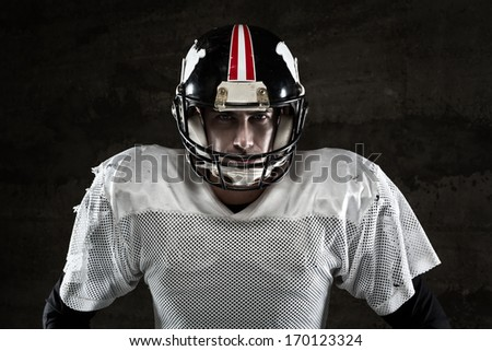 Portrait of american football player looking at camera on concrete background