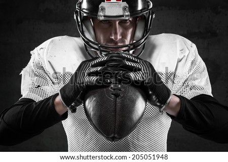 Portrait of american football player on dark background