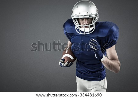 Portrait of American football player running with ball against grey