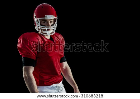 Portrait of american football player wearing his helmet against black background - stock photo