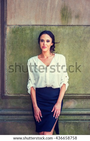 Portrait of American Professional Woman in New York. Beautiful lady, wearing white shirt, black skirt, standing against vintage wall outside, relaxing, taking break. Instagram filtered effect. - stock photo
