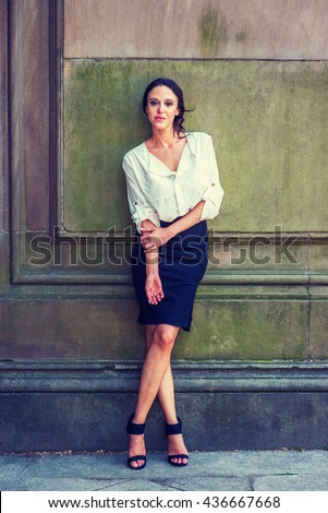 Portrait of American Professional Woman in New York. Beautiful lady, wearing white shirt, black skirt, high heel sandals, standing against vintage wall outside, relaxing. Instagram filtered effect. - stock photo