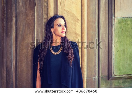 Portrait of American Professional Woman in New York. Lady with long black hair, wearing black dress, necklace, standing by vintage wall outside, thinking, looking forward. Instagram filtered effect.  - stock photo