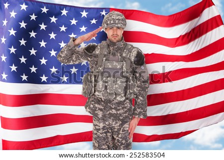 Portrait Of American Soldier Saluting In Front Of Flag - stock photo