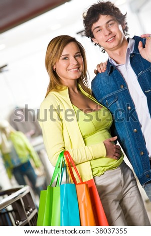 Portrait of amorous couple looking at camera with happy smiles - stock photo