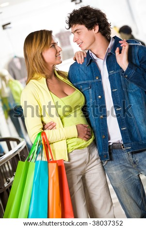 Portrait of amorous couple looking at each other with smiles during shopping