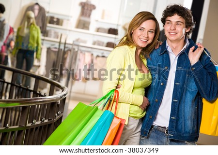 Portrait of amorous couple looking at something with smiles during shopping - stock photo
