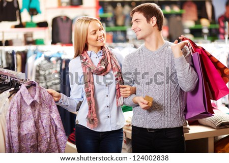 Portrait of amorous couple of shoppers choosing clothes - stock photo