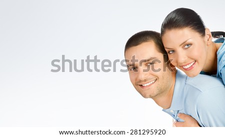 Portrait of amorous young couple, with copyspace blank area for text or slogan, against grey background - stock photo