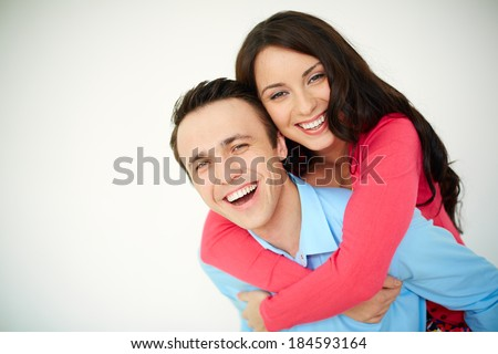 Portrait of amorous young woman embracing her happy husband - stock photo