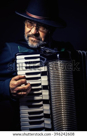 Portrait of an accordion player, playing and posing.  - stock photo