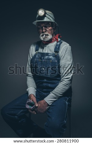 Portrait of an Active Senior Bearded Miner Guy with Smoke on her Mouth, Sitting on a Stool and Holding his Gloves While Looking Straight at the Camera Against Gray Gradient Background.