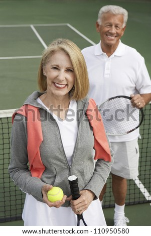 Portrait of an active senior couple on the tennis court - stock photo
