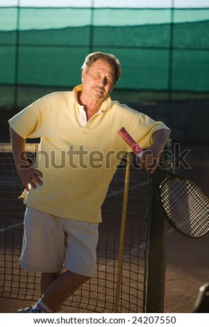 Portrait of an active senior man in his 70s on the tennis court.