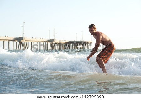 portrait of an active young man surfing in the ocean - stock photo
