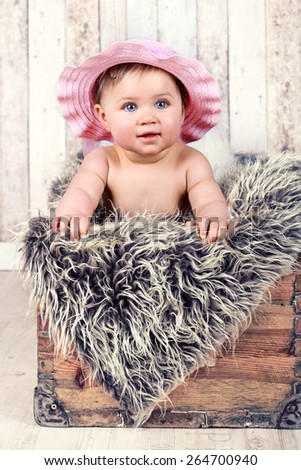 Portrait of an adorable baby Girl, sitting in a old wooden crate wearing a straw hat - stock photo