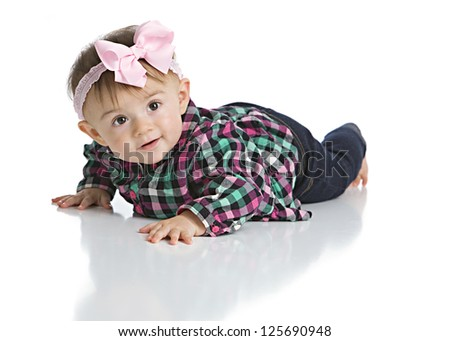 Portrait of an adorable baby girl wearing a plaid shirt, jeans, and a big pink hair bow.  Isolated on white.