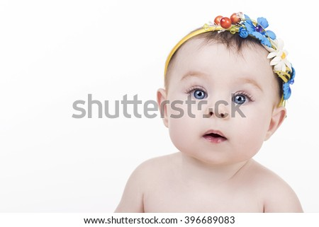 portrait of an adorable baby girl with headband with a decorative flowers. surprised baby child looking into the camera, right view. lovely kid with big blue eyes. happy family concept
