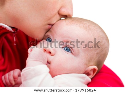 Portrait of an adorable baby kissed by her mother - stock photo
