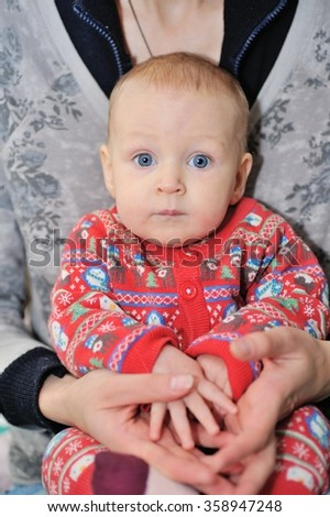 Portrait of an adorable baby/Portrait of an adorable child sitting on hands at mum  - stock photo