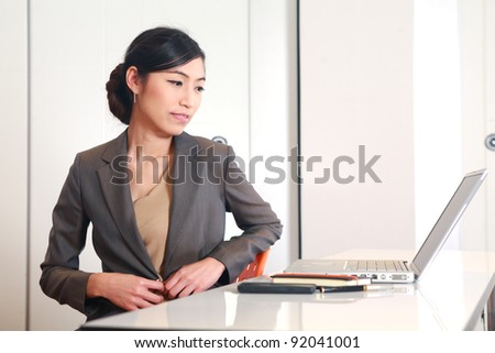 Portrait of an adorable business woman working at her desk with a laptop - stock photo