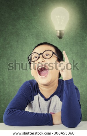 Portrait of an adorable elementary school student wearing glasses and find idea in the classroom, pointing at a bright light bulb - stock photo