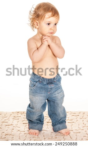 Portrait of an adorable growth baby dressed in denim pants standing barefoot on the carpet on a white background. - stock photo