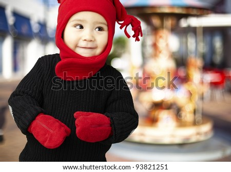 portrait of an adorable kid smiling and wearing winter clothes against a carousel background - stock photo