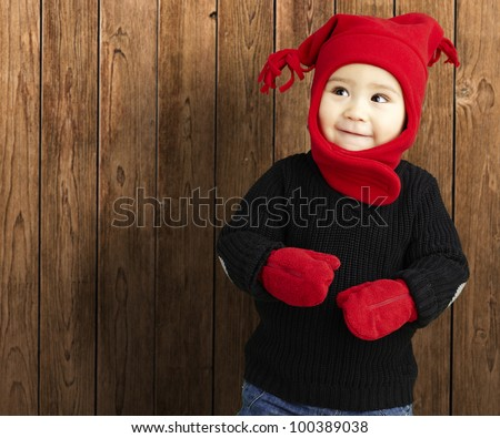portrait of an adorable kid smiling wearing winter clothes against a wooden background - stock photo