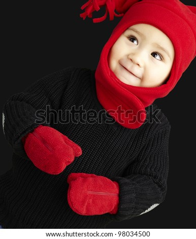 portrait of an adorable kid smiling wearing winter clothes over black background - stock photo