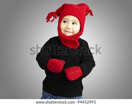 portrait of an adorable kid smiling wearing winter clothes over grey - stock photo