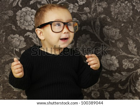portrait of an adorable kid wearing vintage glasses against a vintage background - stock photo