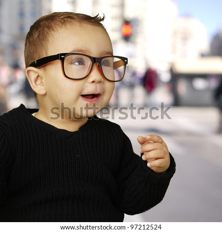 portrait of an adorable kid wearing vintage glasses at a crowded street background - stock photo