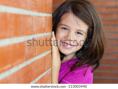 Portrait of an adorable little girl behind a brick wall playing peek a boo