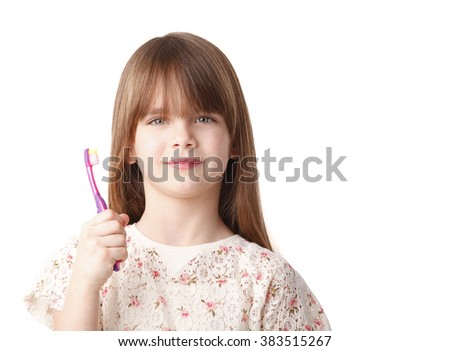 Portrait of an adorable little girl holding a toothbrush while standing at isolated background.