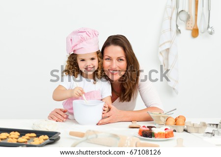 Portrait of an adorable mother and daughter preparing a daughter together in the kitchen - stock photo