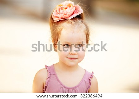 Portrait of an adorable preschool age girl with a hairpin with a flower on her head - stock photo